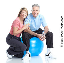 Gym & Fitness. Smiling elderly couple working out. Isolated...