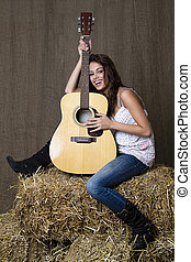 Happy musician - young brunette girl leaning on accoustic...