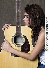 Hugging her guitar - young brunette girl hugging an...