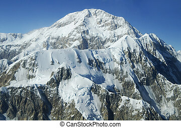 Denali Peaks Under Blue Sky - Rugged snowcapped mountain...