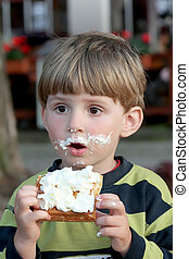Having snack - Boy eating waffle with whipped cream