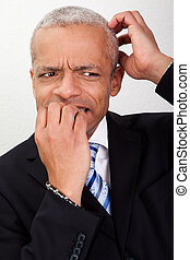 Stressed Businessman Biting His Nails And Scratching His...