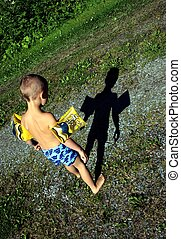 Boy looking at shadow - Little boy wearing shorts and...