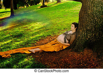Pregnant woman against tree - Horizontal full body portrait...