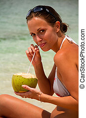 Beautiful woman drinking coconut on beach