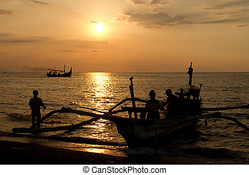 Fishermen at beach during sunset