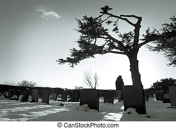 Cemetery - Lonely figure standing amongst tombstones in...