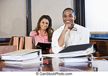 Multiracial businesspeople working on documents - African...
