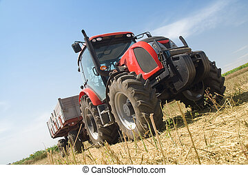 Agriculture - tractor on the field with harvested corn -...