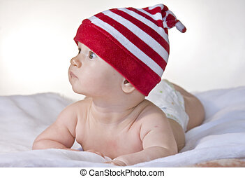 Infant with red hat lying