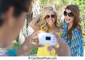 Three Young Women Friends Taking Pictures On Vacation