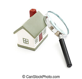 magnifying glass examining model home Isolated on white