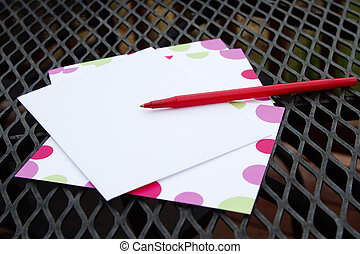 Patio Note - Red pen and note paper placed on black wrought...