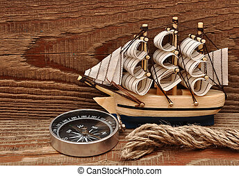 compass, rope and model classic boat on wood background