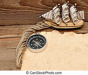 old paper, compass, rope and model classic boat on wood...