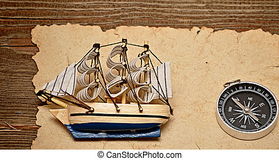 old paper, compass, and model classic boat on wood...