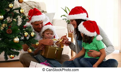 Cute family opening Christmas gift