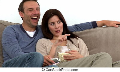 Happy couple watching television with popcorn sitting on the...