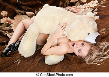 Naked shocked young blonde lying under large teddy bear