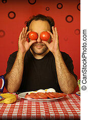 man with tomatoes - bearded man sitting at a table holding...