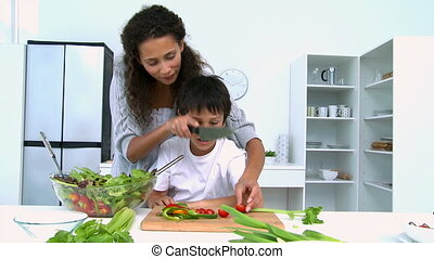 Mother cooking a salad with her son in the kitchen