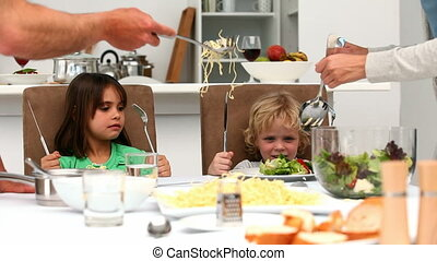 Parents trying to convince kids to eat vegetables in the...