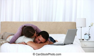 Cute woman hugging her boyfriend while working on laptop on...