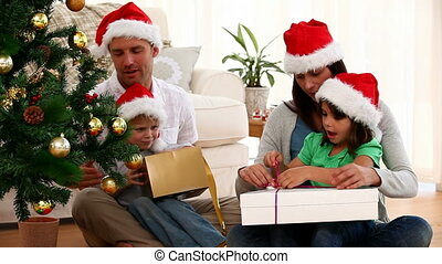 Family opening a christmas gift - Happy family opening a...