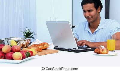 Happy man working on the laptop while having breakfast in...