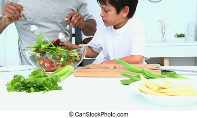 Boy cooking a salad with his father