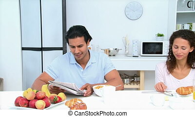 Man reading a newspaper during breakfast with his wife