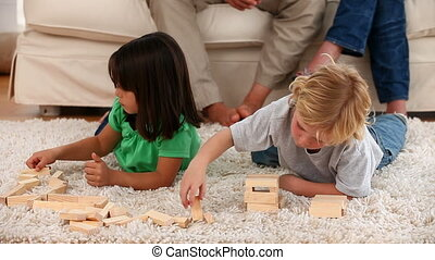 Children playing on the floor while their parents talking...