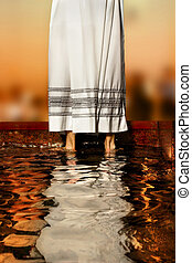 priest's robe - priest's white robe reflecting in baptismal...