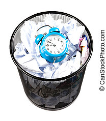 Wasting time - Blue alarm clock sat in a waster paper basket