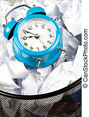 Wasting Time - close up of Blue alarm clock sat in a waster...