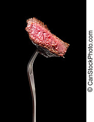 A piece of grilled steak on a fork, isolated on black.