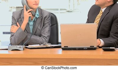 Businesspeople worrying because of a phone call in an office