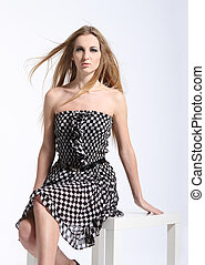Portrait of young beautiful girl in checkered dress -...