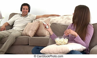 Woman watching tv with popcorn while her husband listens to...