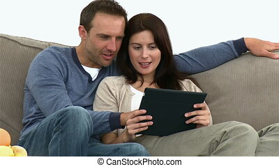 Couple using a computer tablet sitting on the sofa at home