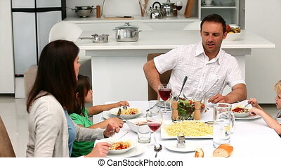 Family having lunch together at the table in the kitchen