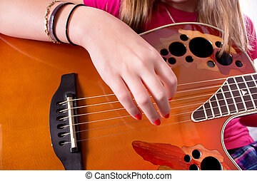 Guitarist - A girl's hand strumming an acoustic guitar