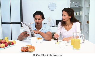Man reading newspaper while having breakfast with his...