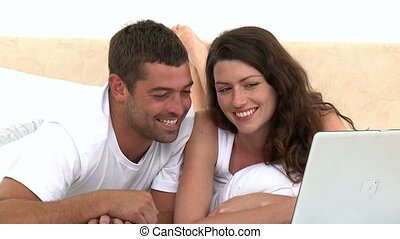 Happy couple using laptop lying on the bed at home