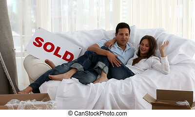 Happy couple relaxing on a bed during their removal