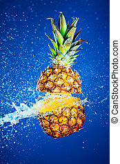 Pineapple splashed with water on a blue background