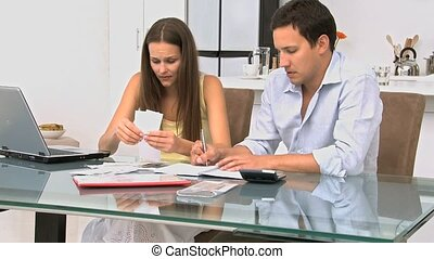 Couple calculating their bills - Worried couple calculating...
