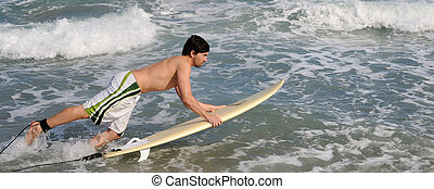 Surfer running on the beach into the ocean with his board