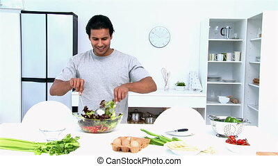 Man smiling at the camera while he preparing a salad in the...