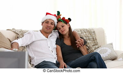 Nice couple watching tv sitting on the sofa in the...